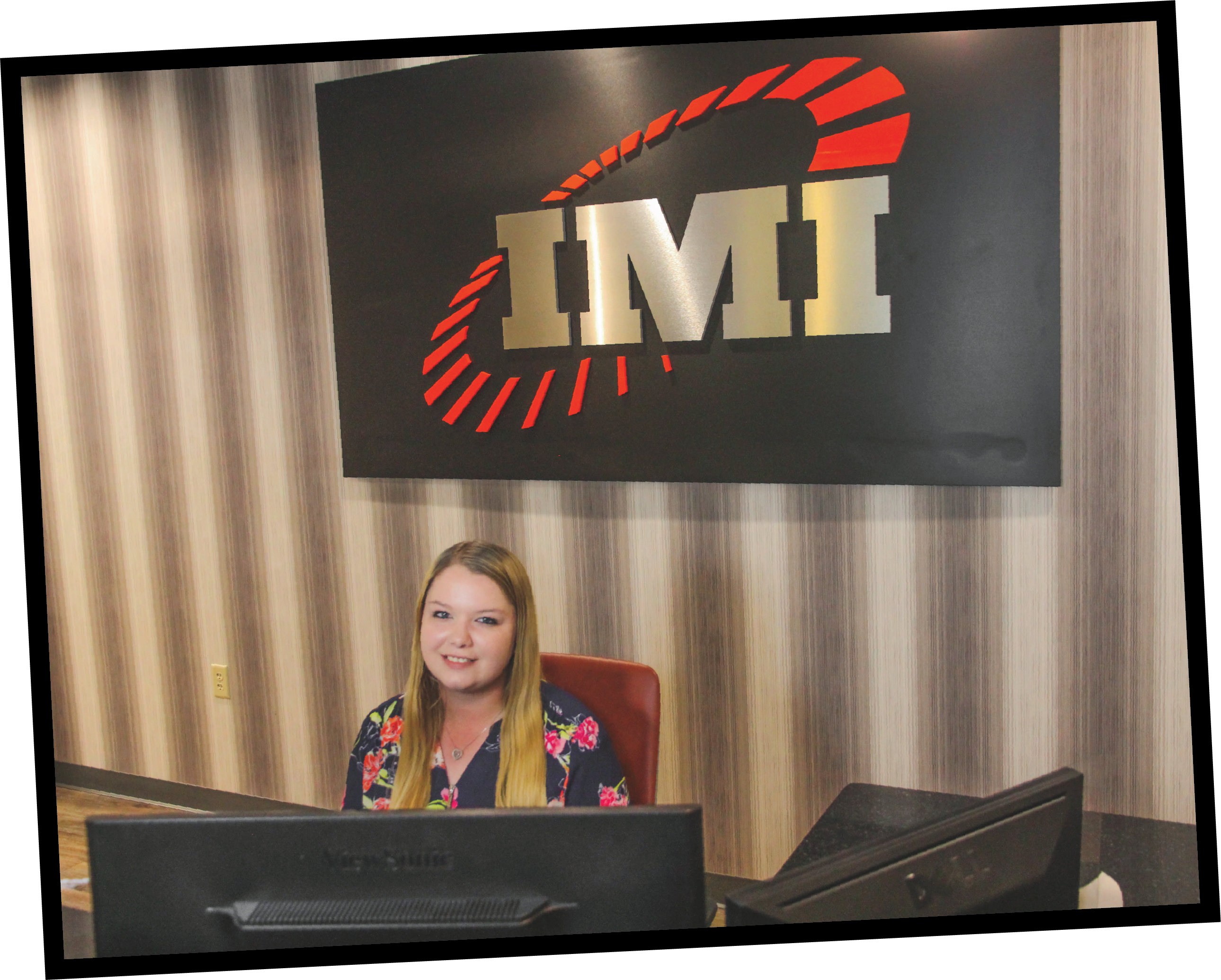 A lady sitting at a desk in front of an IMI sign