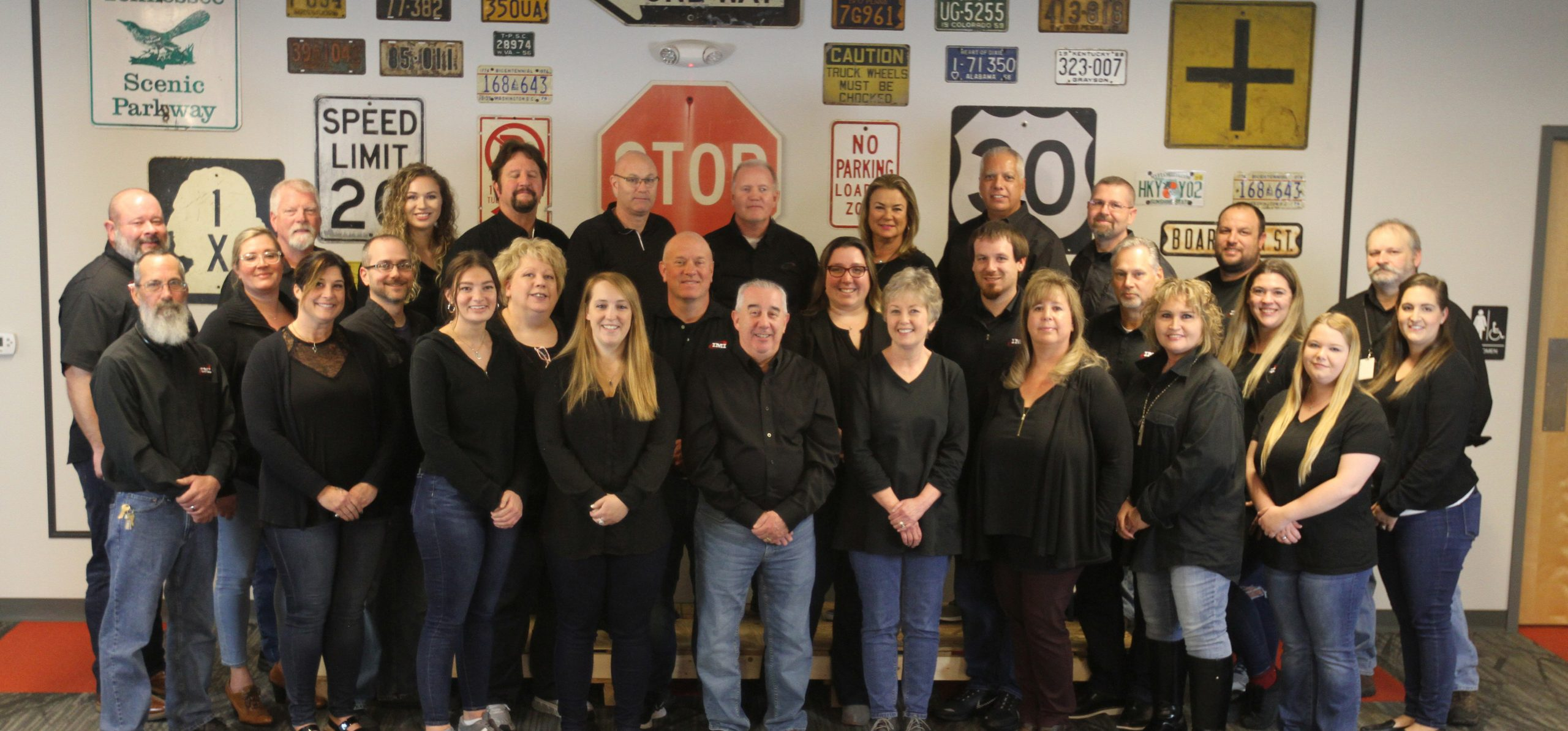 A team picture of everyone in the same black shirt and standing in front of a wall with different road signs